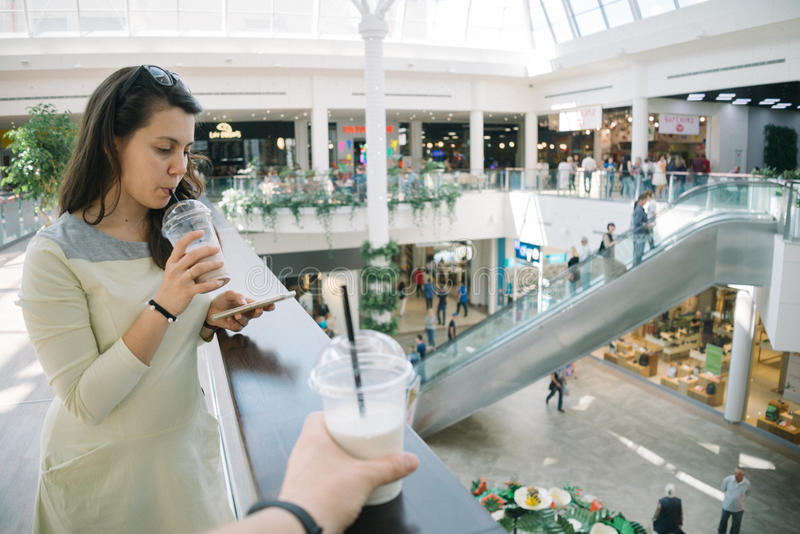 Young woman talking on the phone while walking mall stock images