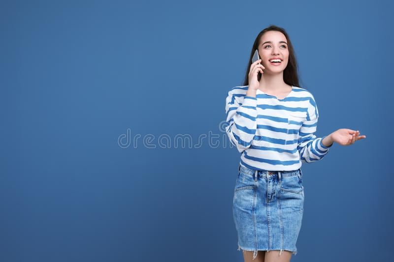 Young woman talking on phone. Against color background stock image