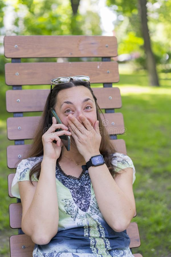 Young woman talking on the smartphone and laughing in the park on the bench Beautiful female relaxing on a park bench and using a stock photography