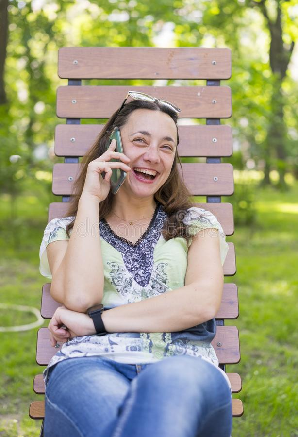 Young woman talking on the smartphone and laughing in the park on the bench Beautiful female relaxing on a park bench and using a royalty free stock images