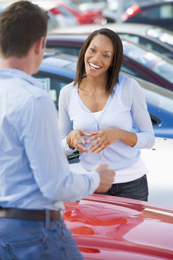 Young woman talking to car salesman royalty free stock images