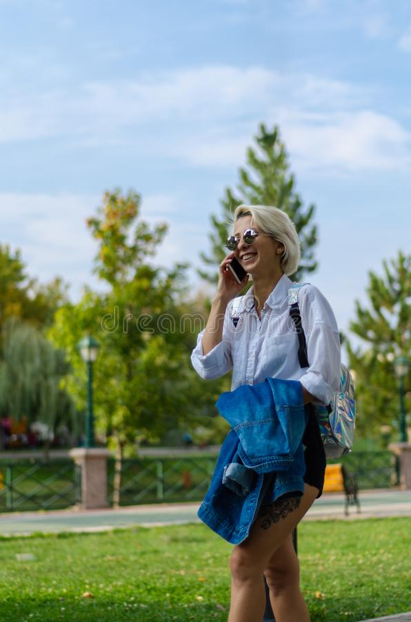 The young woman is talking to the cell phone and walking in the park stock images