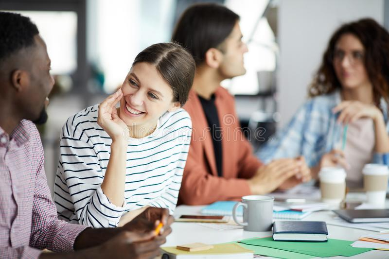 Young Woman Talking to Colleague in Meeting stock image