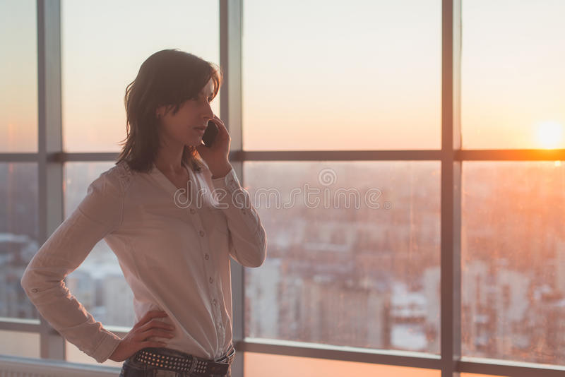 Young woman talking using cell phone at office in the evening. Female businesswoman concentrated, looking forward stock image