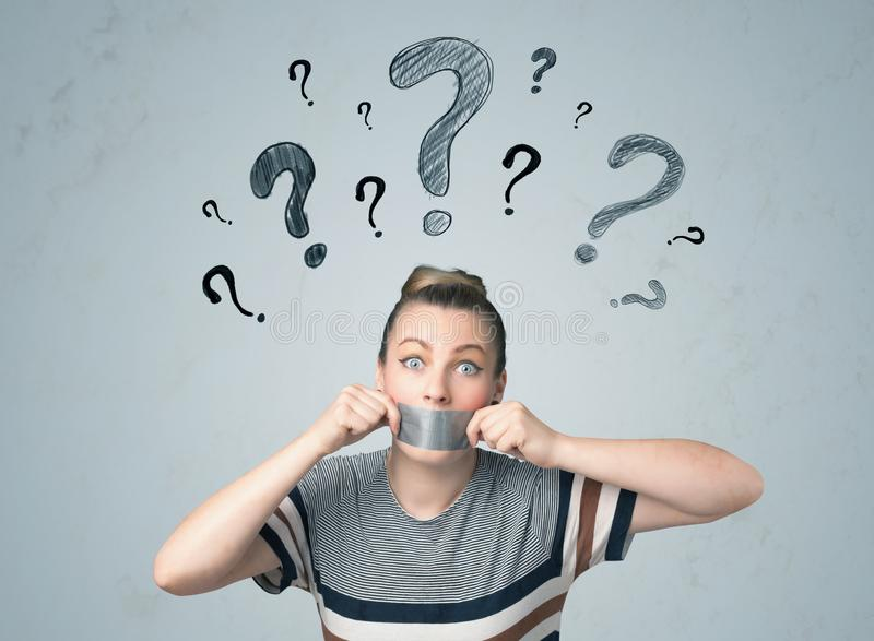 Young woman with glued mouth and question mark symbols. Young woman with taped mouth and question mark symbols around her head royalty free stock image