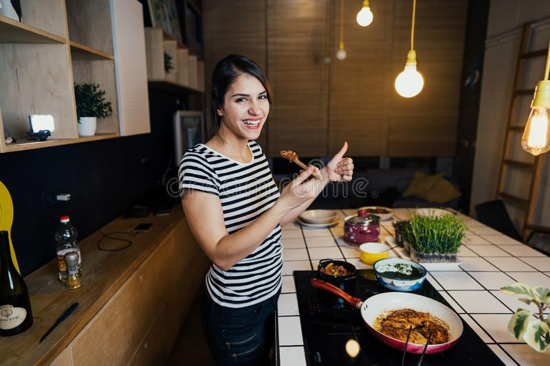Young woman tasting a healthy meal in home kitchen.Making dinner on kitchen island standing by induction hob.Preparing fresh. Vegetables,enjoying spice aromas stock image