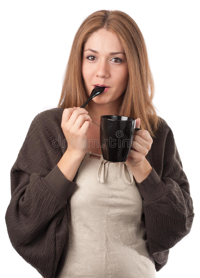 Young woman tasting from a teaspoon stock photography