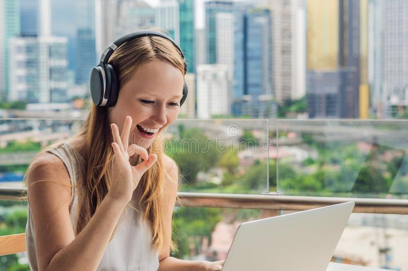Young woman teaches a foreign language or learns a foreign language on the Internet on her balcony against the backdrop of a big. City. Online language school stock image