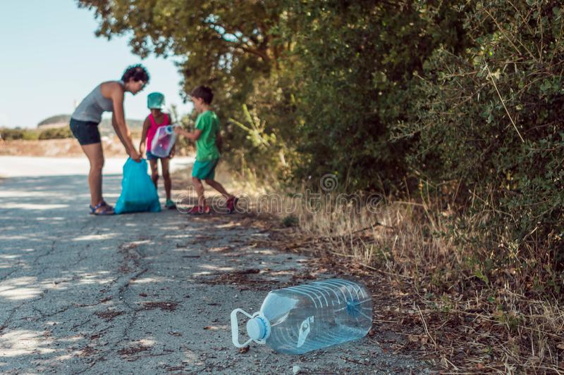 Young woman teaching her children to be environmentally responsible while picking up trash in the countryside. Young women teaching her children to be stock photos