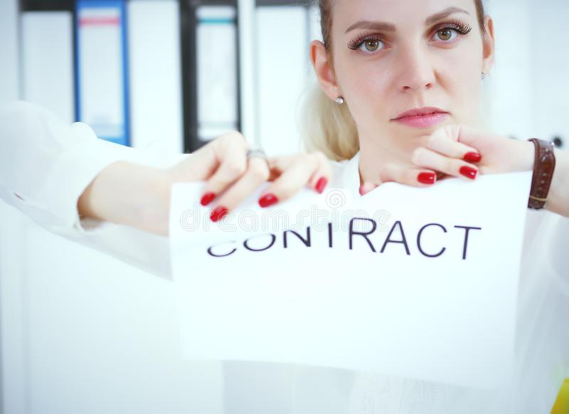 Angry woman tears agreement documents in front of camera closeup. Young woman tears agreement documents in front of camera closeup stock image
