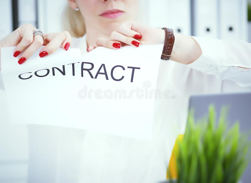 Angry woman tears agreement documents in front of camera closeup. Young woman tears agreement documents in front of camera closeup royalty free stock photos