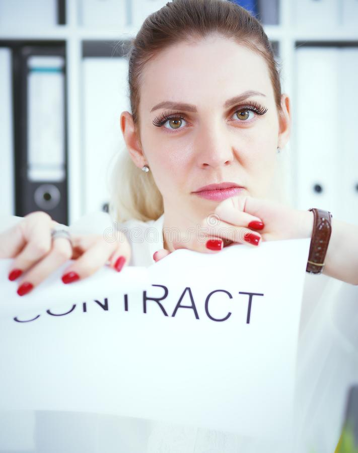 Angry woman tears agreement documents in front of camera closeup. Young woman tears agreement documents in front of camera closeup stock photo