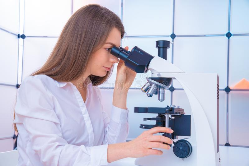 Young woman technician is examining a histological sample, a biopsy in the laboratory of cancer research. Scientist analyzing microscope slide at laboratory royalty free stock photography