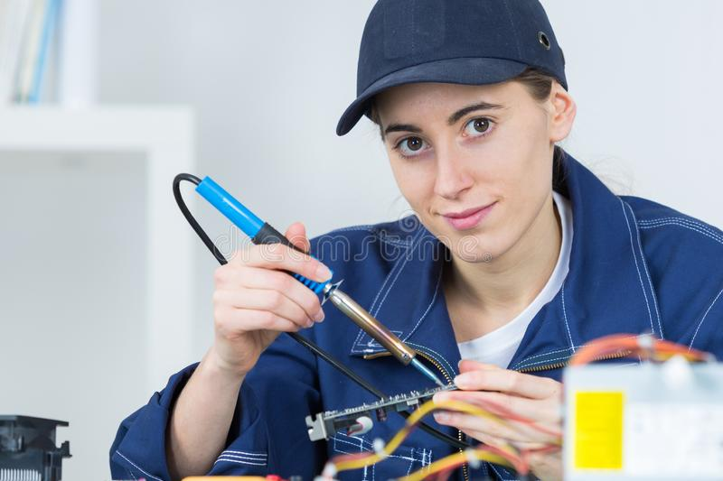 Young woman technician repairing electronics device royalty free stock images