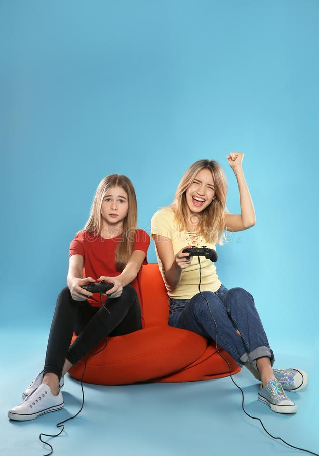 Young woman and teenage girl playing video games with controllers on color background. Young women and teenage girl playing video games with controllers on color stock photos