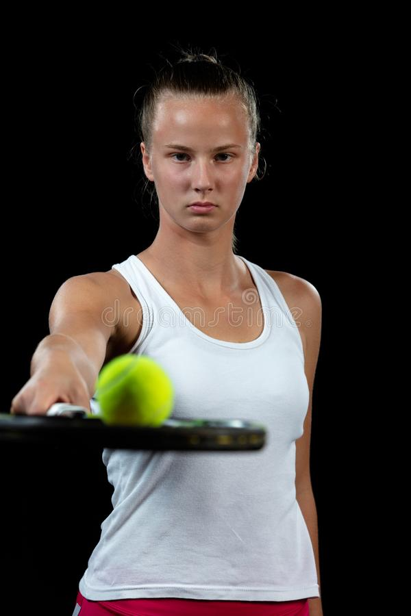 Young woman on a tennis practice. Beginner player holding a racket, learning basic skills. Portrait on black background. stock image