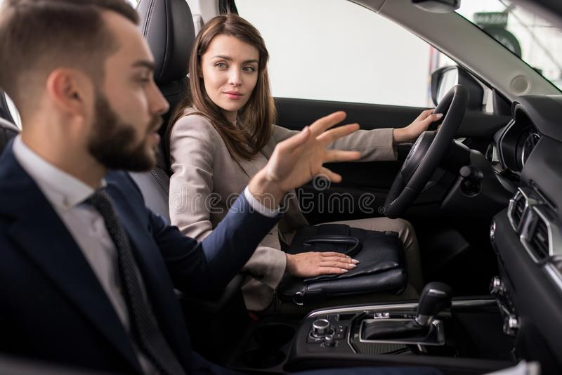 Young Woman Testing New Car in Showroom stock image
