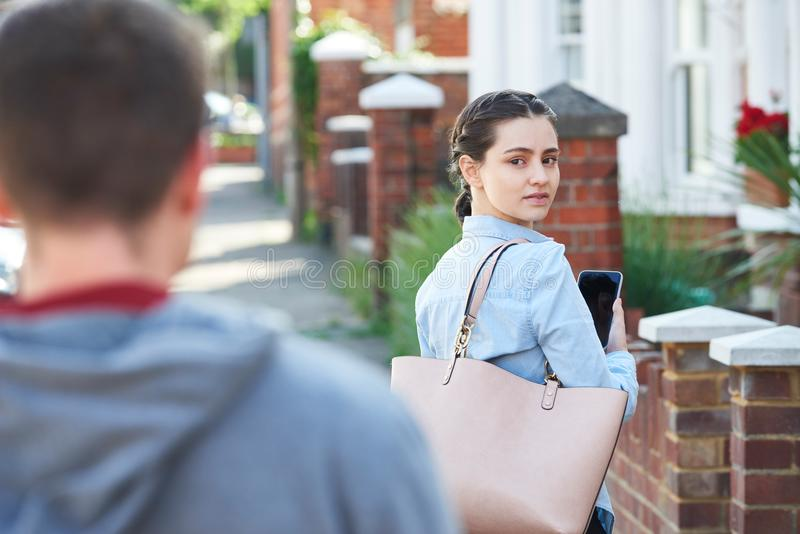 Young Woman Texting For Help On Mobile Phone Whilst Being Stalke stock photo