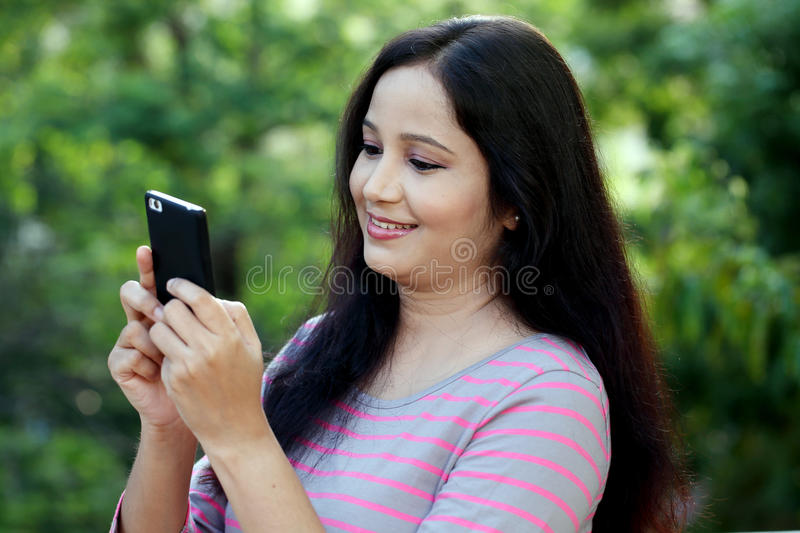 Young woman texting on smartphone at outdoors. Happy young woman texting on smartphone at outdoors stock image