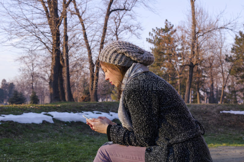 Young woman texting in winter stock images