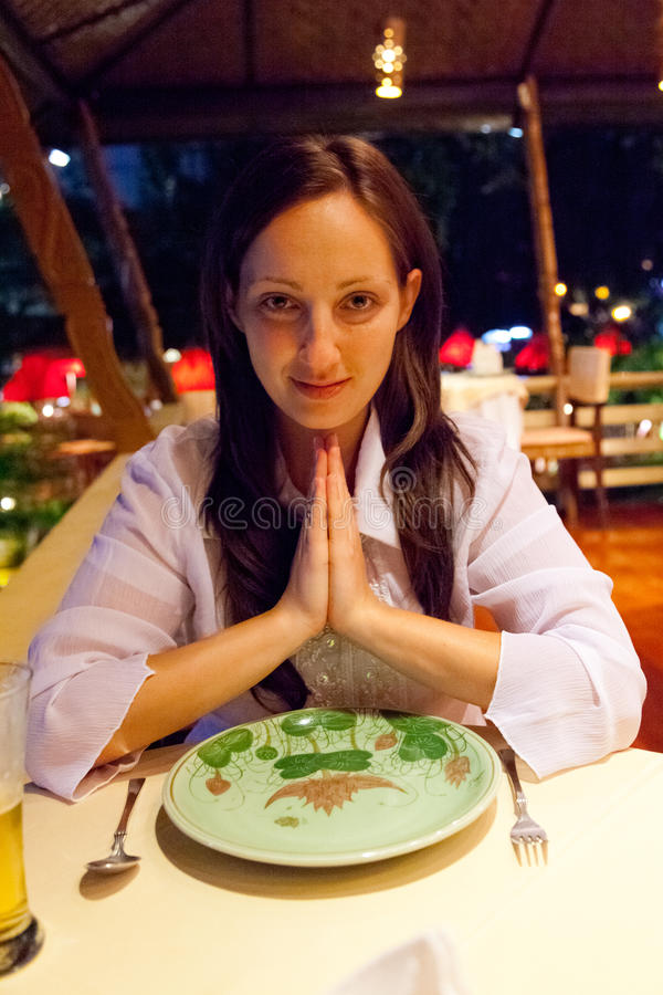 Young woman in Thai restaurant. Young woman having dinner in Thai restaurant in Chiang Mai royalty free stock images