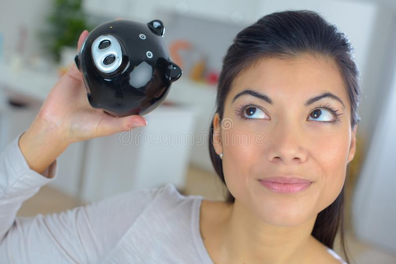 Young woman thinking about future holding piggy bank royalty free stock photo