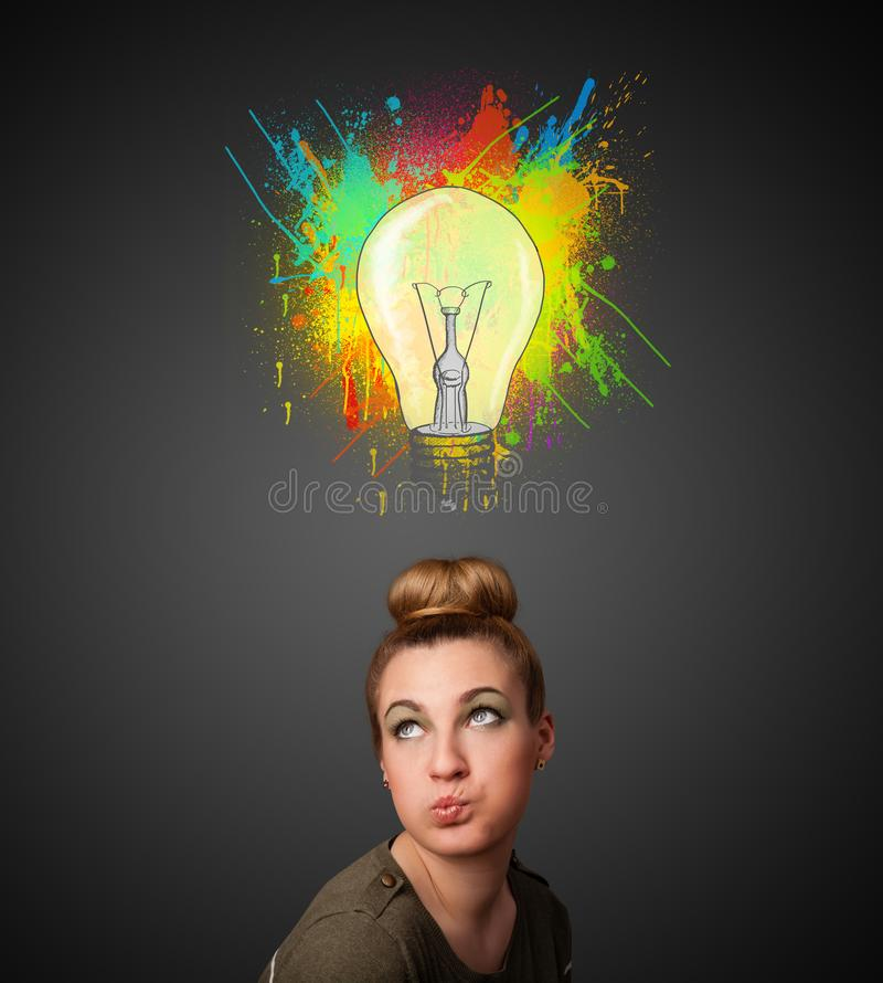 Young woman thinking with lightbulb above her head. Pretty young woman gesturing with lightbulb and paint splashes above her head stock photos