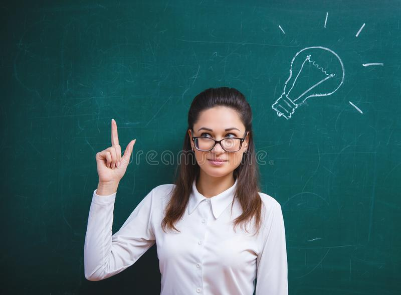 Young woman thinks next to the board royalty free stock images