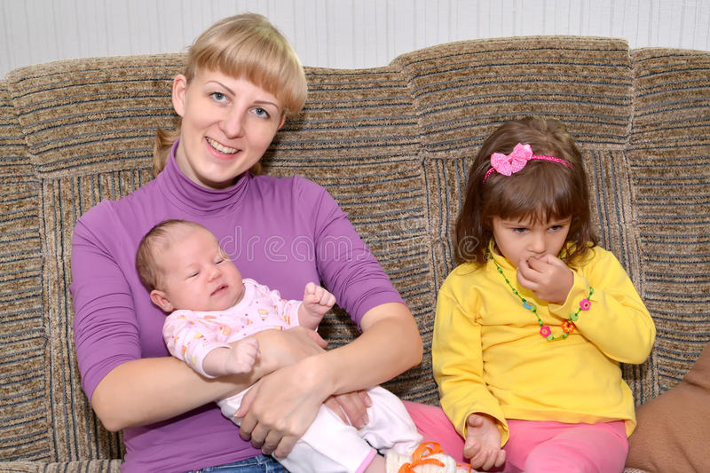 The young woman with the three-year-old daughter and the baby sis on a sofa. The young women with the three-year-old daughter and the baby sits on a sofa royalty free stock image