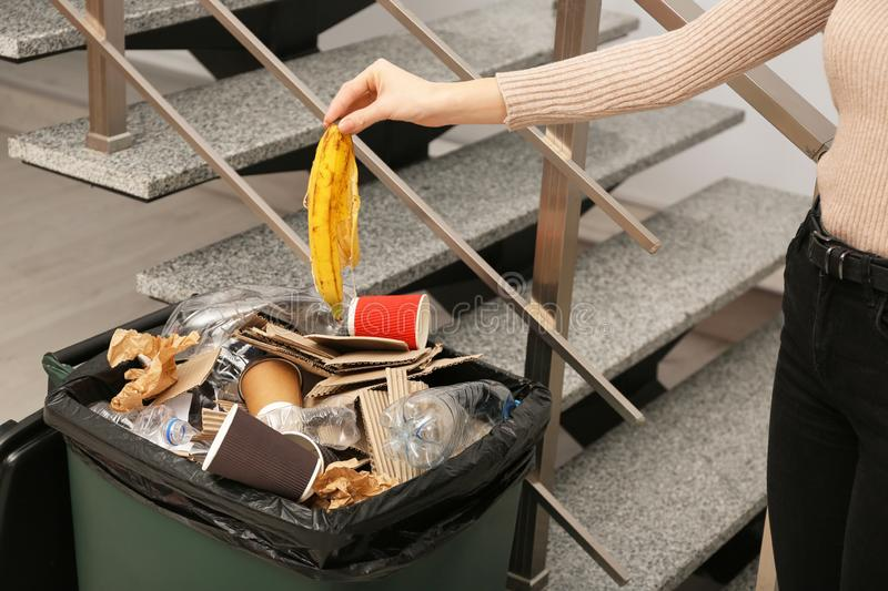 Young woman throwing banana peel in trash bin indoors, closeup. Waste recycling royalty free stock photography