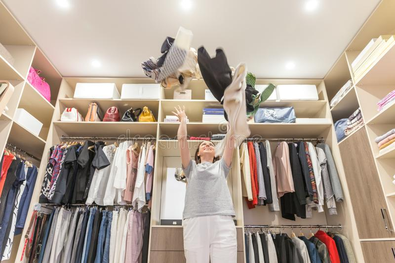 Young woman throwing clothes in walk in closet. Mess in wardrobe and dressing room royalty free stock image