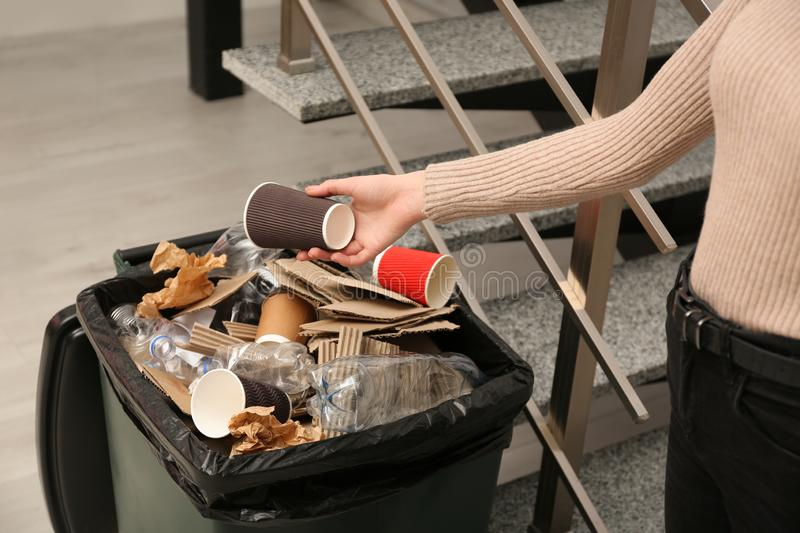 Young woman throwing coffee cup in trash bin indoors, closeup. Waste recycling stock image