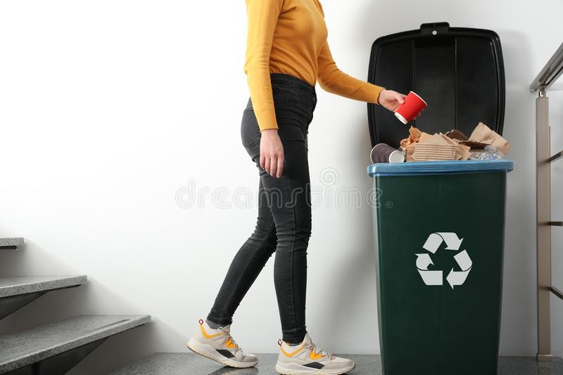 Young woman throwing coffee cup in trash bin indoors, closeup. Waste recycling stock photography