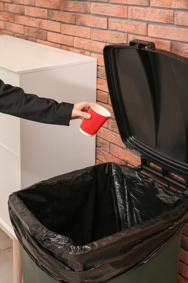 Young woman throwing coffee cup in trash bin indoors, closeup. Waste recycling royalty free stock photos