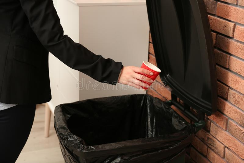 Young woman throwing coffee cup in trash bin indoors, closeup. Waste recycling royalty free stock photography
