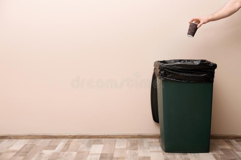 Young woman throwing coffee cup in trash bin indoors, space for text. Waste recycling stock images