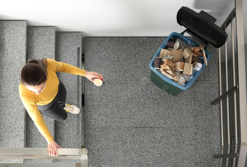 Young woman throwing coffee cup in trash bin indoors, top view. Waste recycling stock image