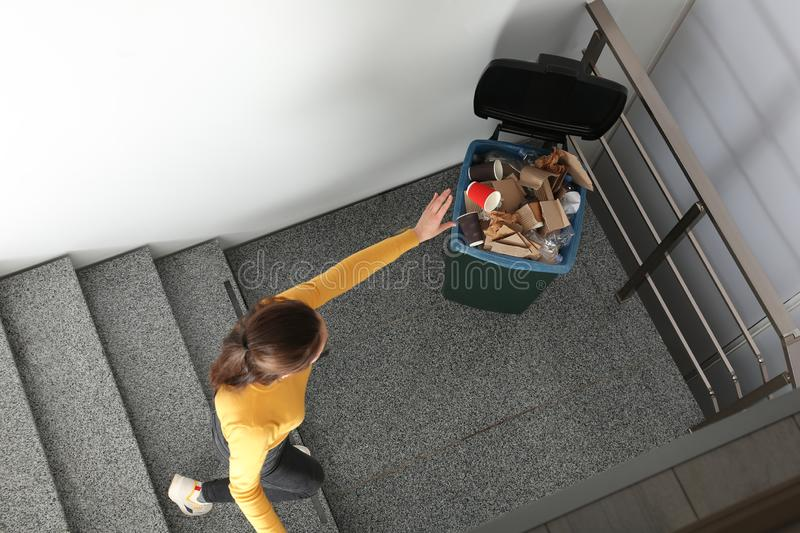 Young woman throwing coffee cup in trash bin indoors, top view. Waste recycling royalty free stock photography