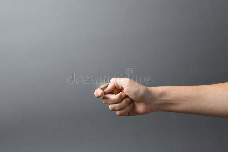 Young woman throwing coin on grey background. Closeup stock photo