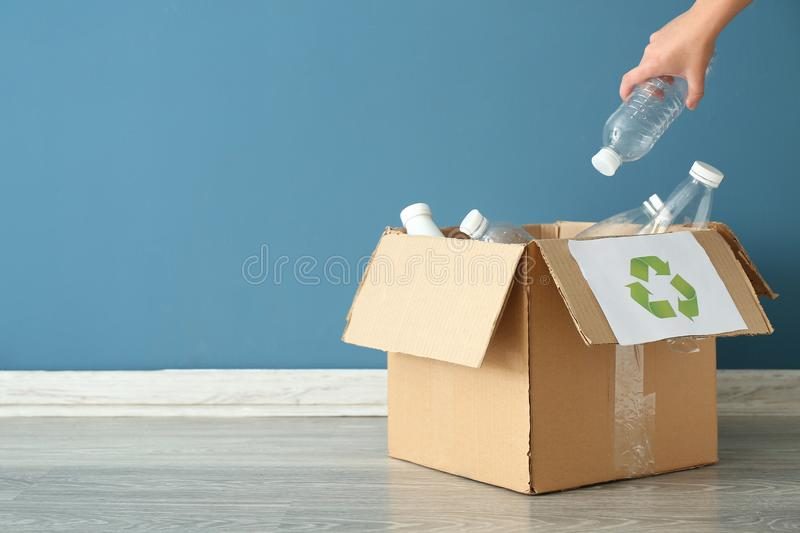 Young woman throwing plastic bottle into cardboard box indoors. Recycling concept stock photography