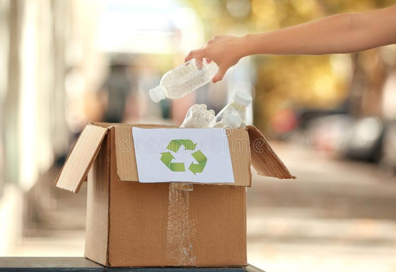 Young woman throwing plastic bottle into cardboard box outdoors. Recycling concept royalty free stock images