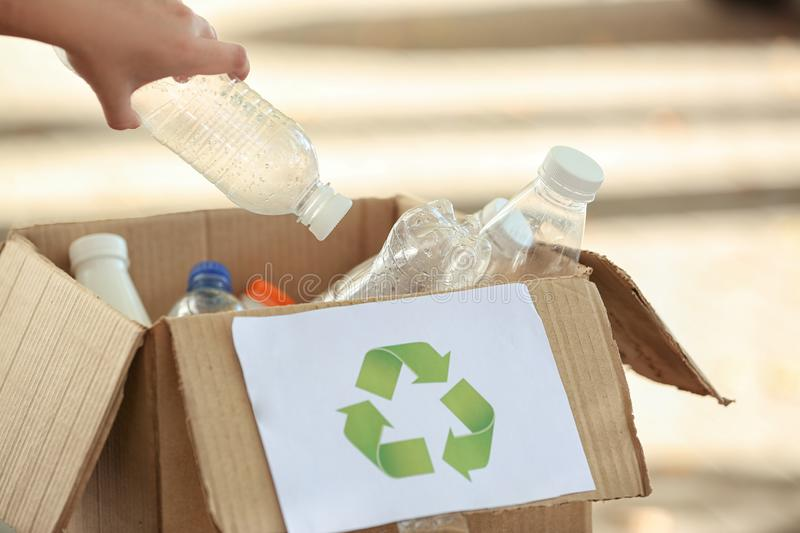 Young woman throwing plastic bottle into cardboard box outdoors. Recycling concept stock photography