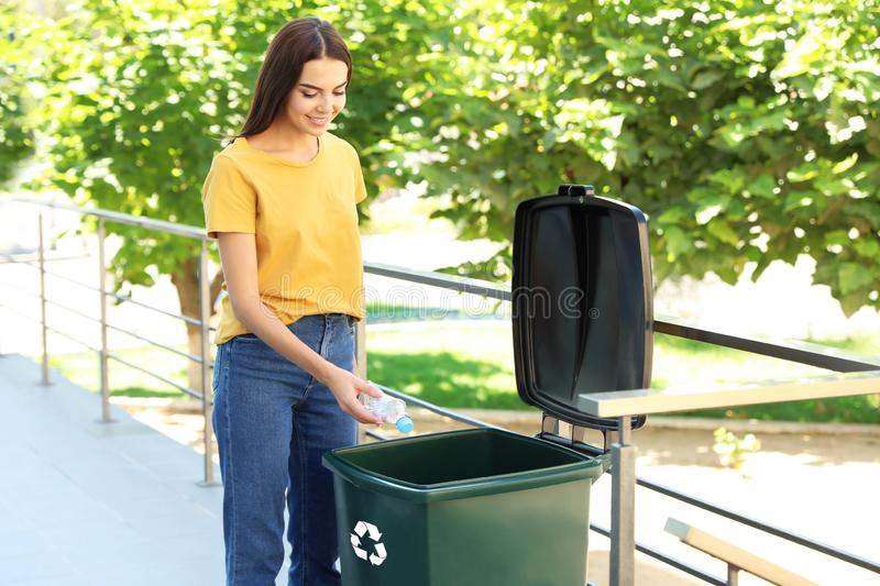 Young woman throwing plastic bottle into recycling bin. Outdoors stock images