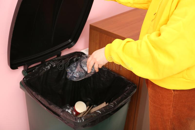 Young woman throwing plastic bottle in trash bin indoors, closeup. Waste recycling stock images