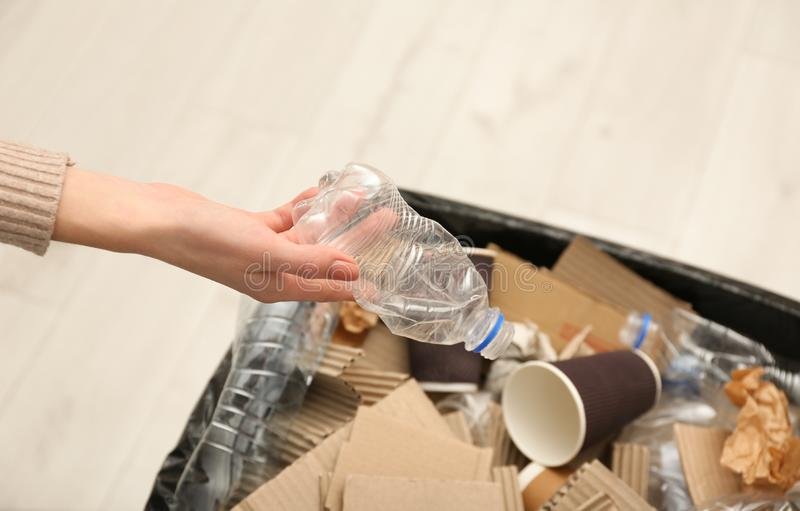 Young woman throwing plastic bottle in trash bin indoors, closeup. Waste recycling royalty free stock photography