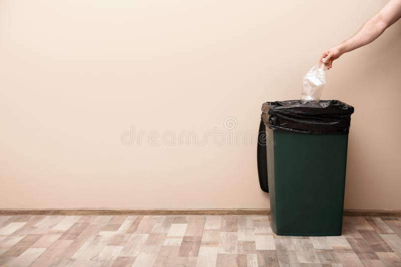 Young woman throwing plastic bottle in trash bin indoors, space for text. Waste recycling stock images