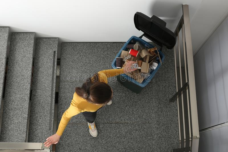 Young woman throwing plastic bottle in trash bin indoors. Top view. Waste recycling royalty free stock photo