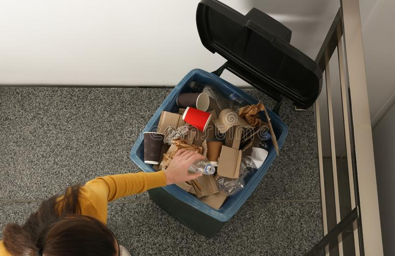 Young woman throwing plastic bottle in trash bin indoors, top view. Waste recycling stock photos