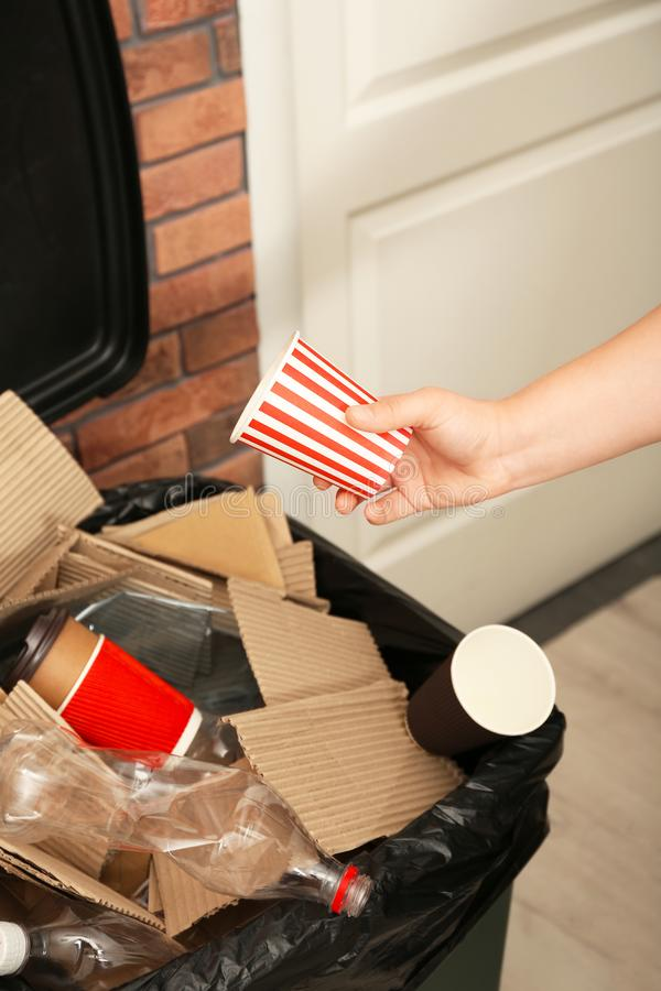 Young woman throwing popcorn cup in trash bin indoors, closeup. Waste recycling royalty free stock photo