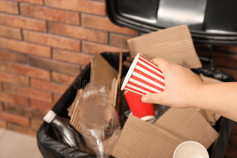 Young woman throwing popcorn cup in trash bin indoors, closeup. Waste recycling royalty free stock photography